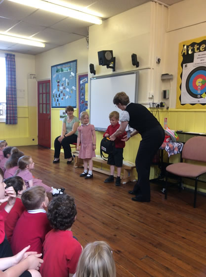 Kay Reeve [right] presenting the defibrillator to pupils and staff of Terrington St John's Junior School