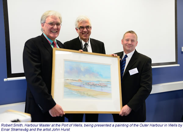 Robert Smith, Harbour Master at the Port of Wells, being presented a painting of the Outer Harbour in Wells by Einar Strømsvâg and the artist John Hurst.