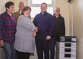 Ross McMilan [2nd from right] being shown the battery storage 
